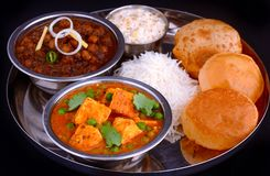 Indian Punjabi meal-curries served with rice and puri. Indian thali- assortment of dishes served for meal for lunch or dinner.It consists of matar paneer or Stock Images