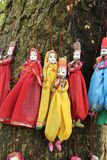 Indian puppets for sale. Typical string indian puppets made for the tourist market hang from the bark of a tree royalty free stock photo