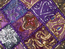Indian quilt. Purple indian embroidered fabric featuring purple squares and gold embossed patterns Royalty Free Stock Images
