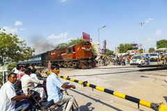 Indian Railway train passes a level crossing. JAIPUR, INDIA - OCTOBER 23: Indian Railway train passes a railroad crossing on October 23, 2012 in Jaipur, India Royalty Free Stock Image