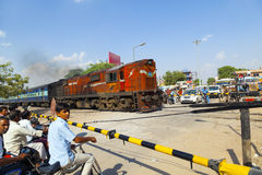 Indian Railway train passes a railroad crossing Royalty Free Stock Image