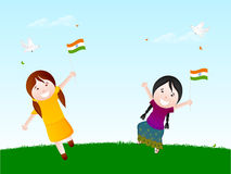 Indian Republic Day celebration with cute girls. Cute little girls holding National Flags with flying pigeons celebrating Indian Republic Day on nature Royalty Free Stock Photo