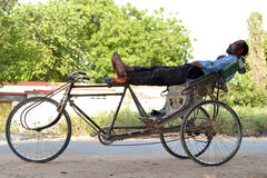 An indian rickshaw puller resting in strange position Stock Photos