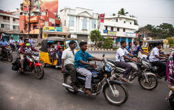 Indian riders ride motorbikes on busy road Stock Image
