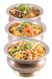 Indian risotto biryani in metal or bronze bowls on white background Stock Images