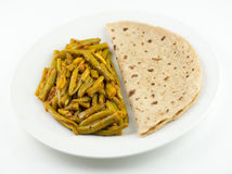 Indian roti and green bean sabzi on white background Stock Photos