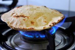 An Indian roti or tortilla on a gas stove being cooked. stock photography