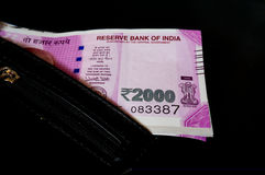Indian rupee 2000 notes in black leather wallet. New Indian rupee 2000 note placed in a black leather wallet and isolated on black. The new currency has been Royalty Free Stock Image