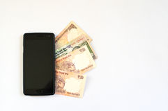 Indian rupee under a mobile Royalty Free Stock Image
