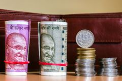 Indian rupees. Banknotes and stacked coins. Leather wallet in background stock image