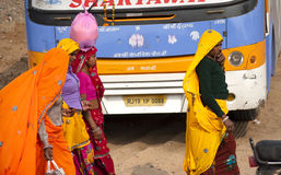 Indian rural women. Walking in front of a bus Royalty Free Stock Photo