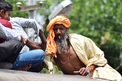 Indian sadhu climbing on train roof Royalty Free Stock Photos