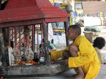 Indian Sadhu (holy man) tending a street shrine. Indian Sadhu (wandering holy man or priest) tending a Ganesha street shrine on Triveni Ghat in Rishikesh, India Stock Image