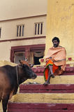 Indian Sadhu with the sacred cow on the steps of the Kshameshwar Ghat in Varanasi Stock Image