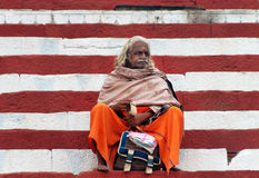 Indian Sadhu sits on the steps of the Kedar ghat near sacred river Ganges in Varanasi Stock Photos
