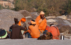 Indian sadhus siting on the beach near River Ganga Stock Image