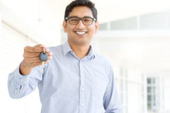 Indian salesman. Young Asian Indian estate agent or salesman showing a key, India male business man, real modern office building as background stock photography