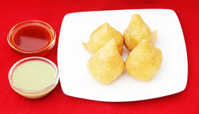Indian Samosa. Images of Indian samosas  in a white plate with sauce and green chatney Royalty Free Stock Photography