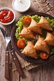 Indian samosa on a plate with sauce closeup, vertical top view Stock Image