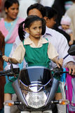 Indian school girl on a scooter. A little girl in school uniform with his father returns home from school on a scooter stopping at one of the many street markets Royalty Free Stock Photos