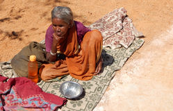 Indian senior blind woman seeks alms or begs on road to temple d Royalty Free Stock Photo