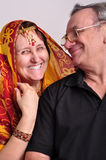 Indian senior couple looking at each other. Portrait of happy senior couple looking at each other. Husband and wife wearing Indian clothing sari, tikka and Royalty Free Stock Photo