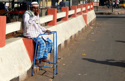 Indian senior physically challenged man seeking help / alms on a busy road. Royalty Free Stock Photo