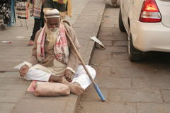 Indian senior physically challenged man seeking help / begging sitting on a busy road Royalty Free Stock Photography