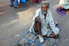 Indian senior physically challenged man seeking help / begging sitting on a busy road Royalty Free Stock Image