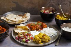 Indian sharing meal. Indian meal with chicken tikka masala, aloo gobi - cauliflower curry, raita, flat breads and salad Royalty Free Stock Photography