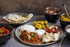 Indian sharing meal. Indian meal with chicken tikka masala, aloo gobi, raita, flatbreads and salad Royalty Free Stock Photos