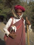 Indian sheperd carrying a lamb. Stock Image