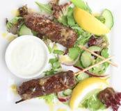 Indian Shish Kebabs with Raita Yoghurt Dip. Indian lamb shish kebabs with salad and raita dip Royalty Free Stock Photo