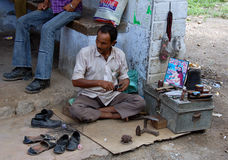 Indian shoe clener. Picture was taken in Himachal Pradesch (India). Man is cleaning a reparing shoes Royalty Free Stock Images