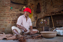 Indian shoemaker. GODWAR REGION, INDIA - 13 FEBRUARY 2015: Elderly Indian shoemaker from Rabari tribe makes new pair of traditional shoes in workshop. Rabari or stock images