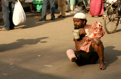 Indian sick beggar seeking help on a busy road. Royalty Free Stock Photography