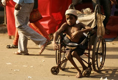 Indian sick and handicapped beggar seeking help on a busy road. Stock Image