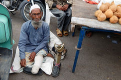 Indian sick and handicapped beggar seeking help on a busy road. Stock Photography