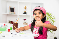 Indian small girl busy in drawing or painting or colouring. Indian girl drawing, indian girl painting,asian girl colouring, paint brush and indian girl royalty free stock photography