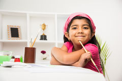 Indian small girl busy in drawing or painting or colouring. Indian girl drawing, indian girl painting,asian girl colouring, paint brush and indian girl stock image