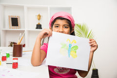 Indian small girl busy in drawing or painting or colouring Stock Photo