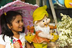 Free Indian Small Girl With Cartoon Statue Smiling While Holding Pink Umbrella Inside Garden, Pune Royalty Free Stock Photos - 144911508