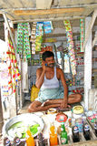 Indian small shop retailer talking on his mobile phone at in his roadside shop. Royalty Free Stock Photos