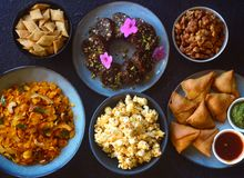Indian Vegan sweet and snacks. Indian snack platter with snacks like namak paare,masala groundnuts, veg samosa,cornflakes chiwda ,and anjeer roll or fig roll and stock photo