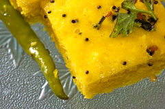 Indian Snacks Dhokla with fried chili. Closeup of Macro of an Indian snacks called Dhokla being served with fried chili Stock Photos