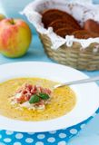 Indian soup with apple, curry, bacon and basil. Indian soup (Potage Mulligatawny) with apple curry, bacon and basil in white soup bowl on blue desk with polka Royalty Free Stock Images