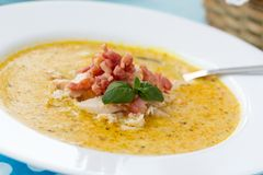 Indian soup with curry, bacon and basil. Indian soup (Potage Mulligatawny) with curry, bacon and basil in white soup bowl on blue desk with polka dot napkin Stock Photo