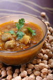 Indian spicy chana masala, raw chickpeas around bowl Stock Photo