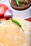 Indian spicy dish, chole bhature topping of green chili Stock Photos