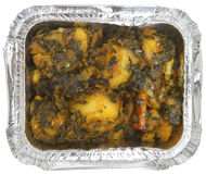 Indian Spinach & Potato Curry Takeaway. Indian spinach & potato curry (sag aloo) in foil takeaway container Royalty Free Stock Image